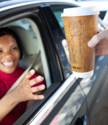 Supply Chain Scene, image of a woman at a drive thru reaching for a disposable drink cup