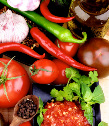 Image of fresh chipotle chili, tomatoes, garlic and ingredients to make salsa