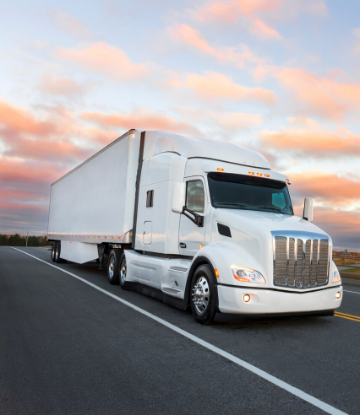 Image of an 18-wheel truck driving on highway at sunset