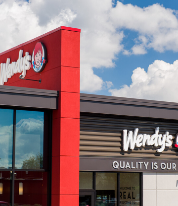 Image of a Wendy's storefront against a blue sky with white clouds