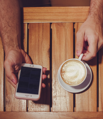 SCS, image of a person with a smart phone in one hand and a coffee cup in the other, sitting at a table