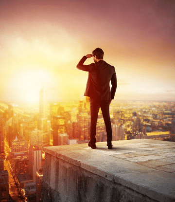 Image of a man standing on top of a building looking toward the sun