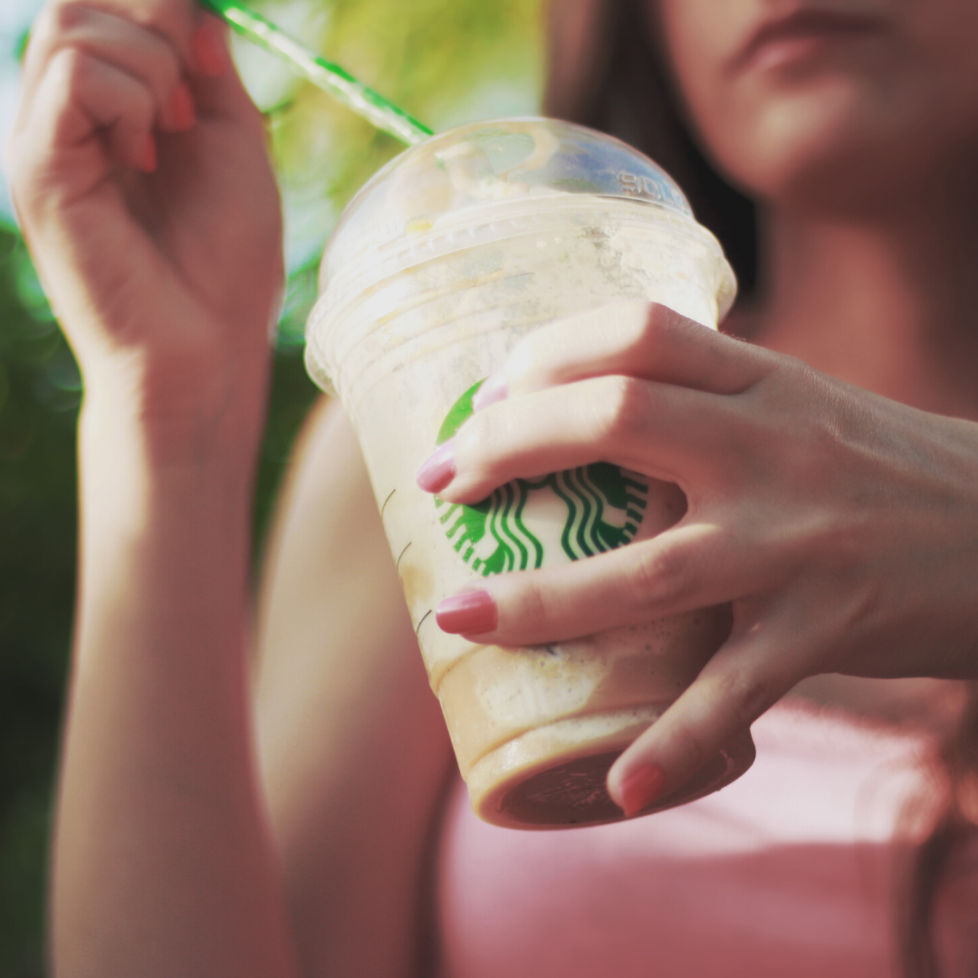 Image of a woman holding a starbucks cold drink cup with a straw