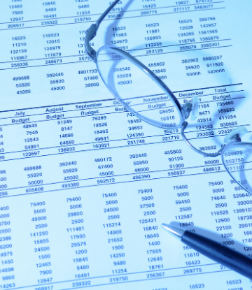 Image of a complex paper budget with glasses and a pen on top