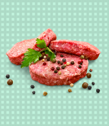 Image of raw hamburgers stacked, with fresh peppercorns