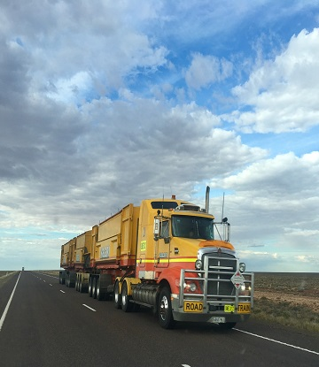 Large yellow semi-truck with vast blue sky and clouds above.