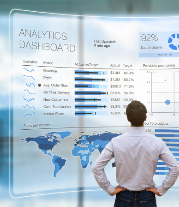 Supply Chain Scene, image of man standing before a wall sized KPI Dashboard
