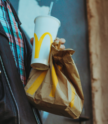 Close up image of a person holding a drink with a McDonald's food bag