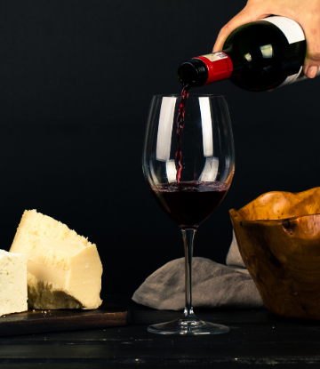 SCS, image of a glass of red wine being poured next to fine cheese wedges