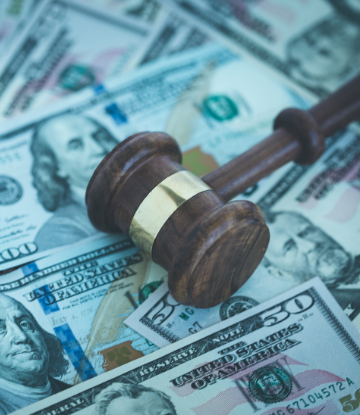 Image of a pile of money with a judge's gavel on top